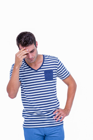 wistfulness: Sad hipster with one hand on head on white background