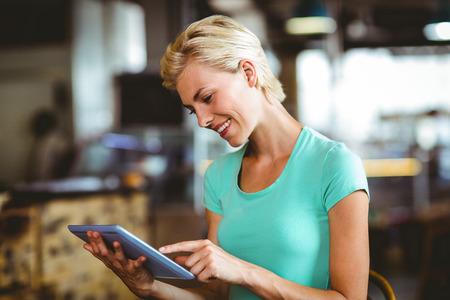 negocios comida: Bonita rubia tomando un café con tablet pc en la cafetería