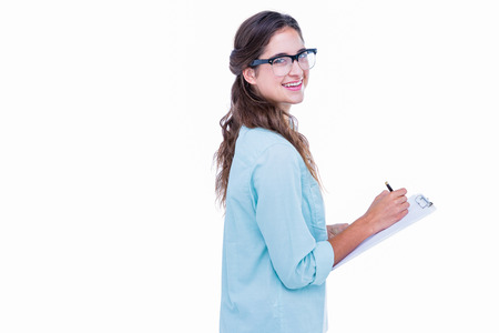 geeky: Pretty geeky hipster writing on notebook and smiling at camera on white background