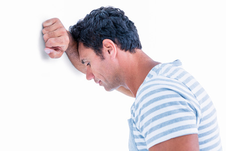 Sad man leaning his head against a wall on white background Banque d'images