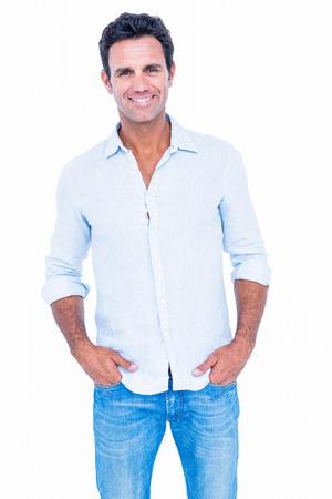 Glücklicher stattlicher Mann, der Kamera mit den Händen in der Tasche auf weißem Hintergrund