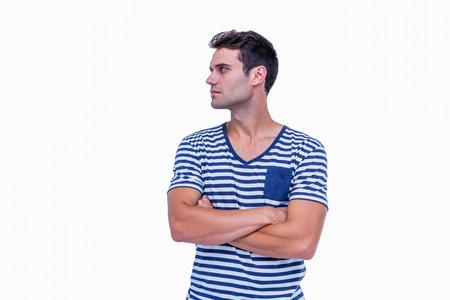 cabello corto: Inconformista hermoso que mira lejos con los brazos cruzados sobre fondo blanco Foto de archivo