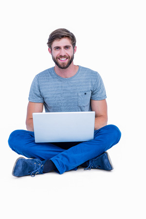 acclamation: Handsome man looking at camera and using laptop on white background Stock Photo