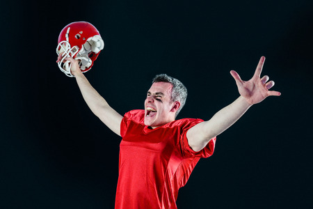 people shadow: A triumph of an american football player without his helmet with black background
