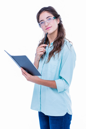 geeky: Thoughtful geeky hipster with a pen against her chin checking her notebook on white background Stock Photo