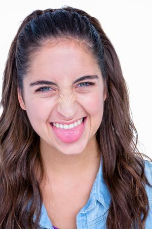 grimacing: Happy brunette grimacing at camera on white background