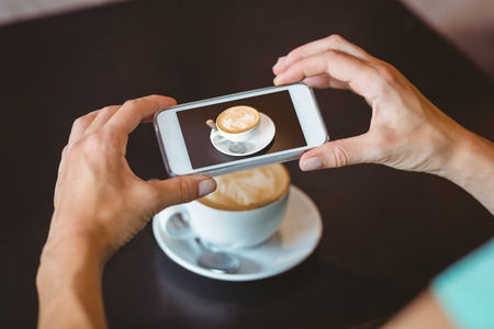 taking picture: Woman taking picture with her smartphone at the cafe