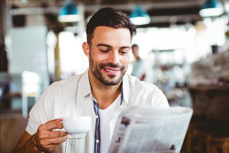periodicos: Hombre joven que come la taza de café lectura periódico en la cafetería