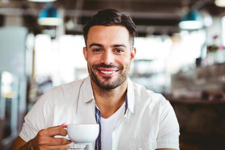 hombre tomando cafe: Hombre hermoso que tiene un caf� en la cafeter�a Foto de archivo