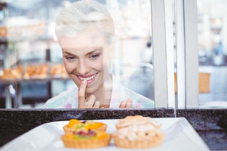 hesitating: Dudando mujer bonita mirando pastel de frutas en la panader�a Foto de archivo