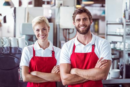 in uniform: Dos baristas sonriendo a la c�mara en el caf� Foto de archivo