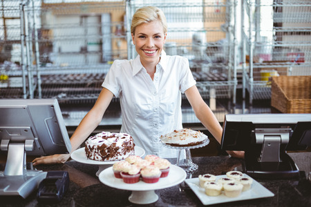 shop owner: Happy pretty woman preparing plate of cake Stock Photo
