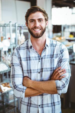 self assured: Selfassured waiter smiling  in front of his bakery