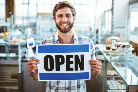 business: 網吧老闆在相機微笑在咖啡館