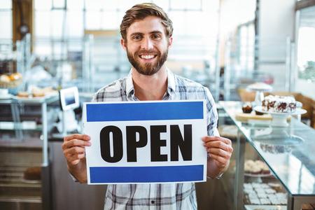 biznes: Właściciel Cafe uśmiecha się do kamery w kawiarni