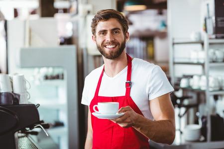hombres guapos: Barista hermoso que sostiene una taza de caf� en el caf� Foto de archivo