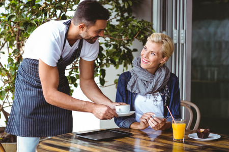 camarero: Bastante ser rubia sirvi� una taza de caf� en el caf� Foto de archivo