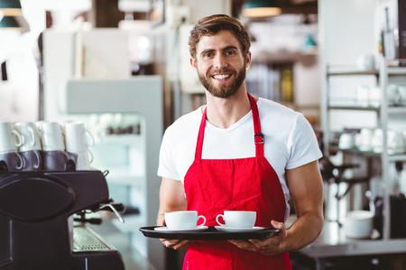 hombres guapos: Barista hermoso que sostiene dos tazas de caf� en la cafeter�a Foto de archivo