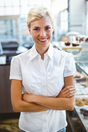 self assured: Selfassured female cook smiling in front of her bakery Stock Photo