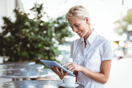woman happy: Happy pretty blonde using tablet computer
