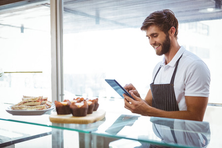 Handsome worker posing on the counter with a tablet at the bakery