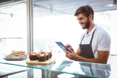 meseros: Trabajador hermoso que presenta en el mostrador con una tableta en la panadería