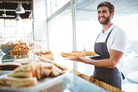 retail business: happy worker holding sandwiches at the backery