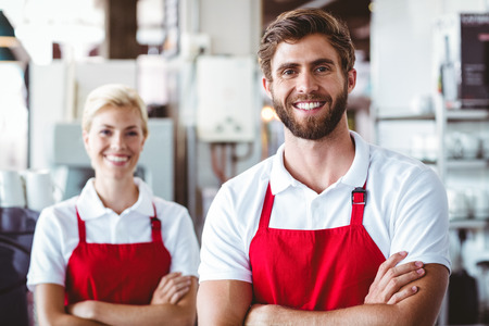 baristas: Two baristas smiling at the camera at the cafe