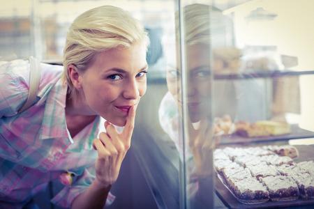 hesitating: Dudando mujer bonita que mira las tortas de la taza en la panader�a Foto de archivo