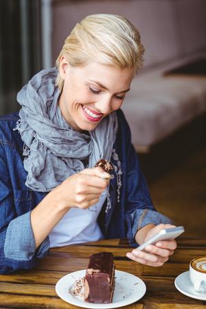 porcion de torta: Rubia sonriente que disfruta de un pedazo de pastel de chocolate en el café Foto de archivo