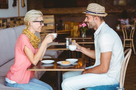 personas platicando: Linda pareja en una cita que habla sobre una taza de caf� en el caf�