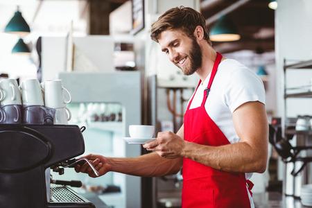 bel homme: Handsome barista préparer une tasse de café avec la machine à café