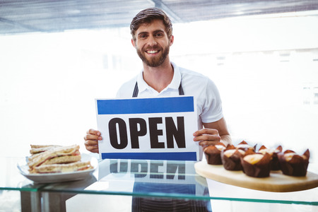 putting up: Smiling worker putting up open sign at the bakery Stock Photo
