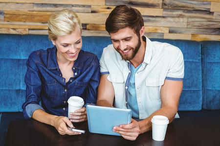 parejas amandose: Linda pareja en una fecha viendo fotos en una tablilla en el café