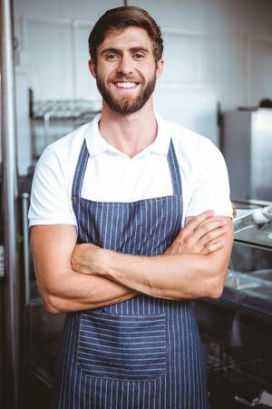 mandil: Sonreír servidor en el brazo delantal cruzó en la panadería