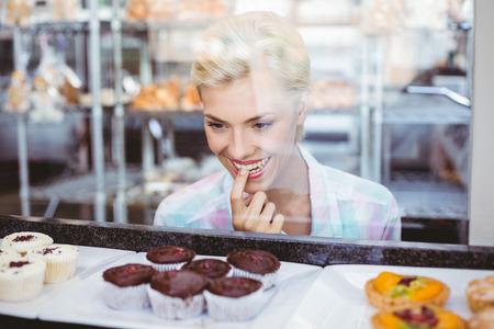 dudando: Dudando mujer bonita que mira las tortas de la taza en la panader�a Foto de archivo