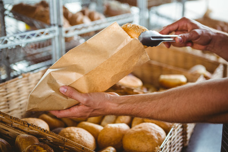Smiling waiter taking bread with tongs at the bakery Stock Photo