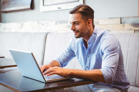 cool guy: Smiling businessman using his laptop at the cafe