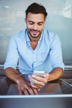 happy customer: Smiling businessman using phone while working on laptop outside the cafe Stock Photo
