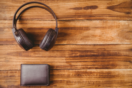 coordinating: Music headphone next to wallet on wooden table