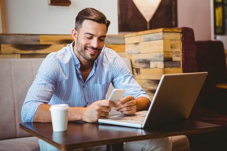 ropa casual: Sonriente hombre de negocios el envío de un mensaje de texto con la computadora portátil junto en el café