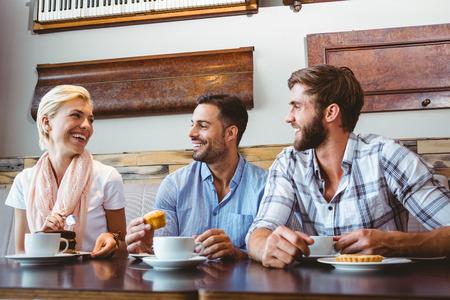 trato amable: Amigos que toman una taza de caf� en el caf�