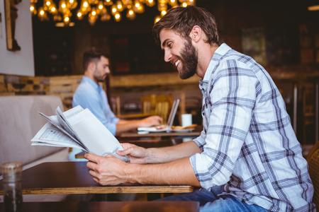 periódicos: Hombre joven que lee un periódico en una cafetería Foto de archivo