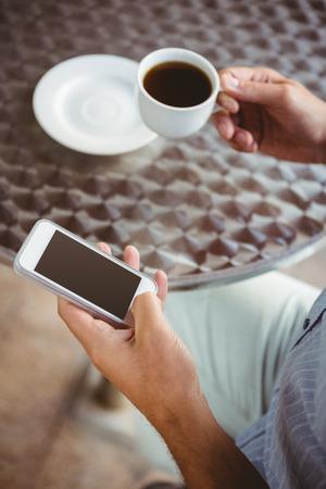 一杯のコーヒーを保持しながらクローズ アップ実業家テキスト メッセージの表示 写真素材