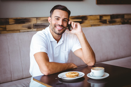 happy customer: Portrait of young man smiling on the phone at the cafe