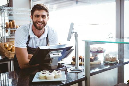 camarero: Trabajador sonriente posando detr�s del mostrador de la panader�a