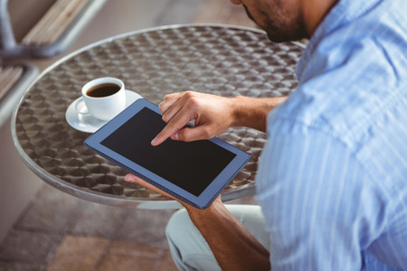 view to outside: Shoulder view of attentive businessman using a tablet outside the cafe Stock Photo