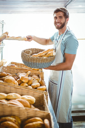 happy worker: Portrait of happy worker holding basket of bread at the bakery Stock Photo