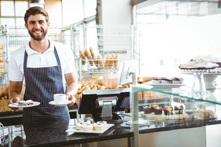 waiter: Smiling worker prepares breakfast at the bakery Stock Photo