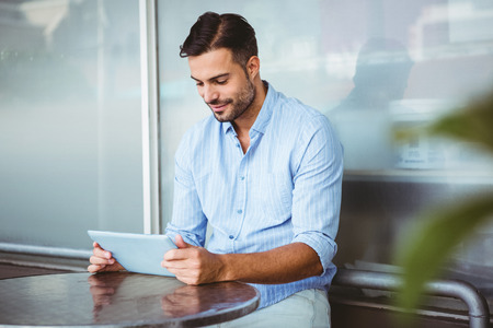handsome man: Smiling businessman using a tablet outside the cafe Stock Photo